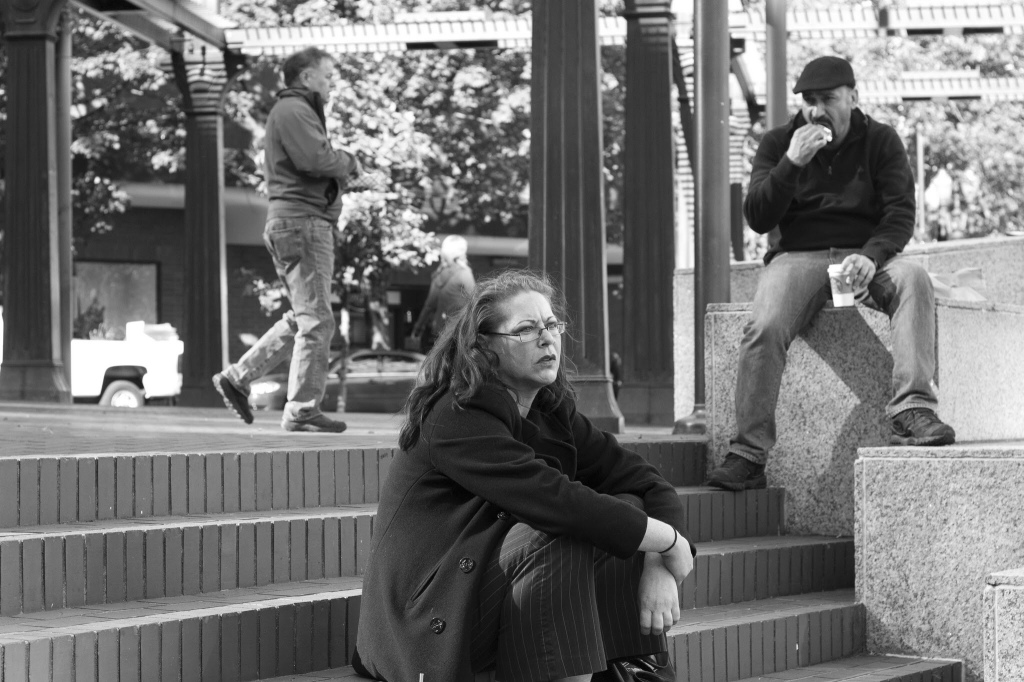 Lunchtime in Portland's Pioneer Courthouse Square. Three people site in the courthouse square.